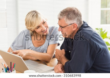 Smiling business team working together on laptop at office