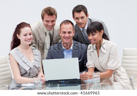 Smiling business team working with a laptop in an office