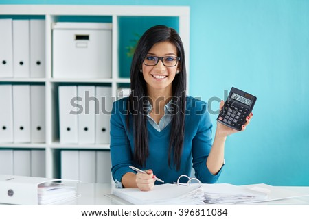Smiling business woman calculates tax at desk in office  - stock photo