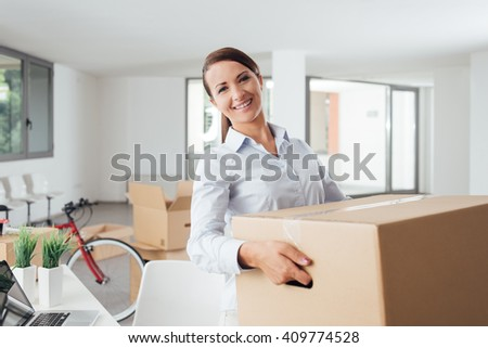 Smiling business woman carrying cardboard boxes into her new office, she is smiling at camera - stock photo