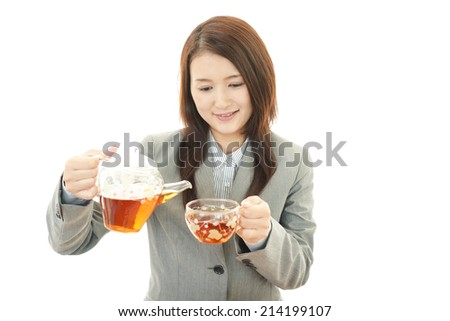 Smiling business woman drinking tea.