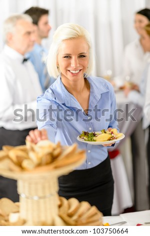 Smiling business woman during company lunch buffet hold salad plate - stock photo