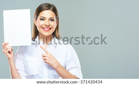 Smiling business woman finger pointing on sign board. Beautiful female model. - stock photo