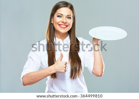 Smiling business woman  holding empty white plate with thumb up. Studio isolated portrait of young business woman. - stock photo