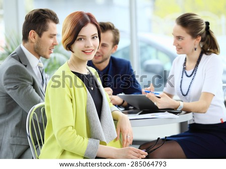 Smiling business woman in foreground  and her co-workers discussing business matters in the background