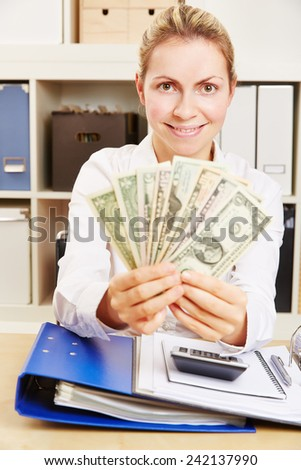 Smiling business woman in office with many Dollar money bills - stock photo