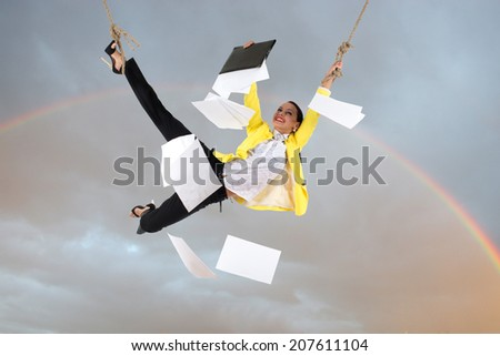 Smiling business woman is hanging on the rope against the sky with rainbow