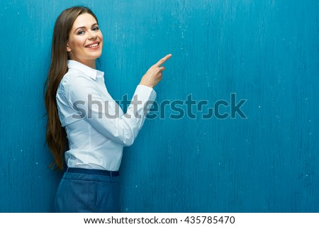 Smiling business woman pointing finger at copy space. White shirt. Long hair. Blue wall. - stock photo