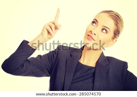 Smiling business woman pointing up. - stock photo