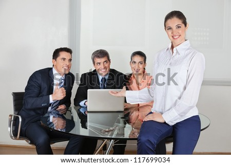 Smiling business woman presenting her office team with laptop computer - stock photo