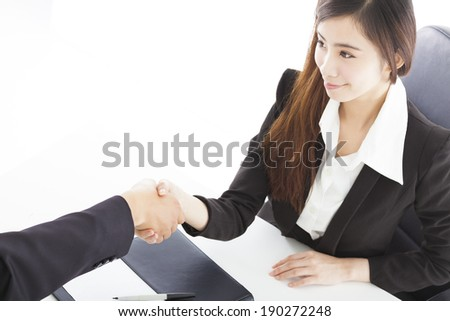 smiling business woman shaking hands with client in her office - stock photo