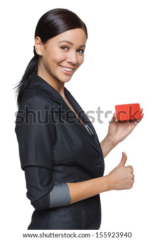 Smiling business woman showing credit card and gesturing thumb up,  isolated on white background - stock photo