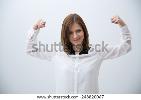 Smiling business woman showing her strength over gray background