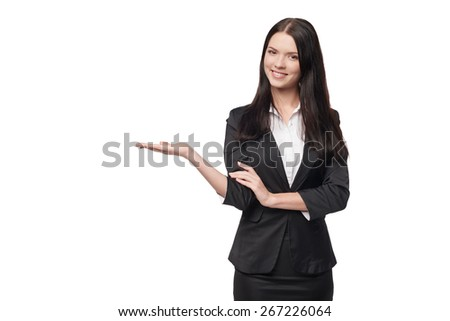 Smiling business woman showing open hand palm with copy space for product or text