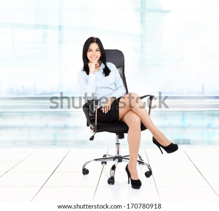Smiling business woman sitting in chair modern office building. young businesswoman smile - stock photo