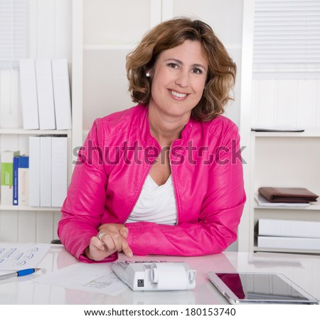 Smiling business woman sitting satisfied at desk. - stock photo