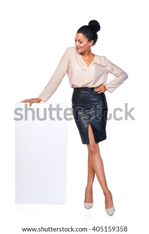 Smiling business woman standing leaning at blank white banner in full length, over white background - stock photo