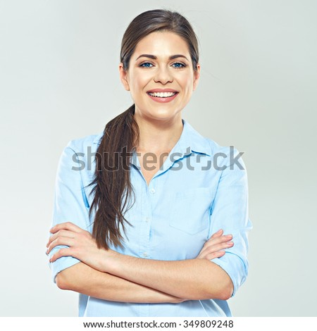Smiling business woman with crossed arms standing against gray studio isolated background.