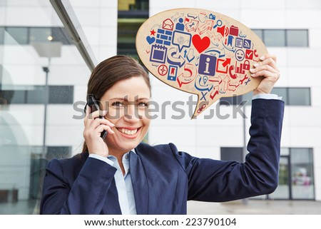 Smiling business woman with smartphone holding speech bubble with digital icons - stock photo
