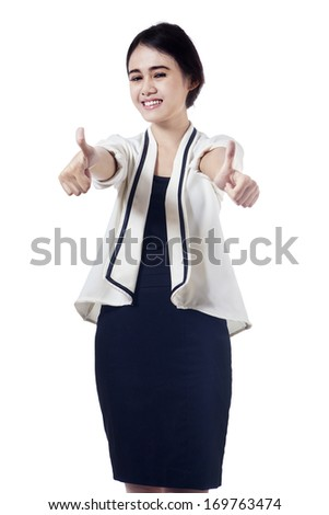 Smiling business woman with thumbs up looking at the camera - stock photo