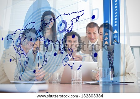 Smiling business workers looking at blue map interface in a meeting - stock photo