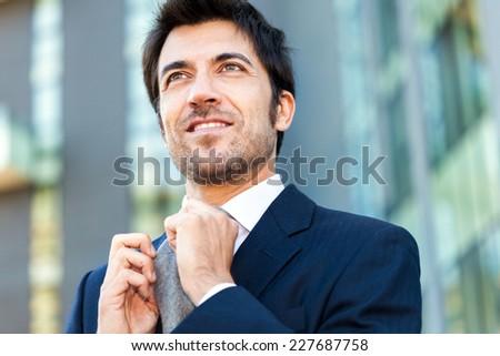 Smiling businessman adjusting his necktie - stock photo