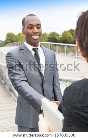 Smiling businessman and businesswoman or client handshaking