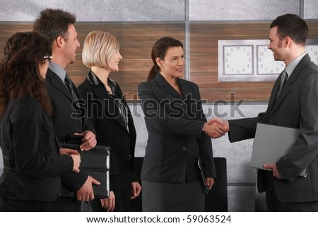 Smiling businessman and businesswoman shaking hands in office.? - stock photo