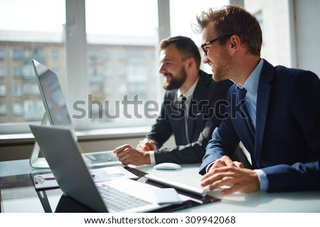 Smiling businessman and his colleague looking at computer monitor at meeting