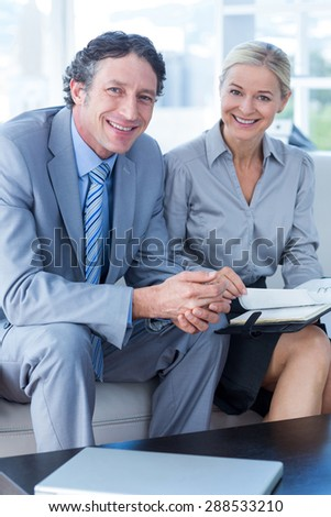 Smiling businessman and his secretary looking at diary in living room