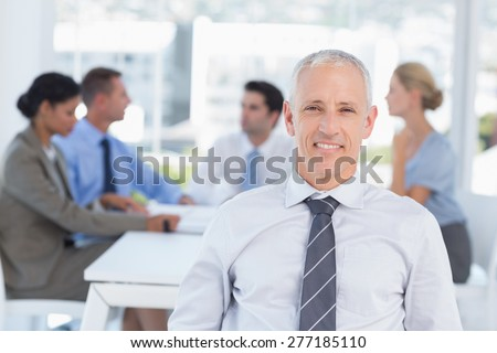 Smiling businessman and his team in the office - stock photo