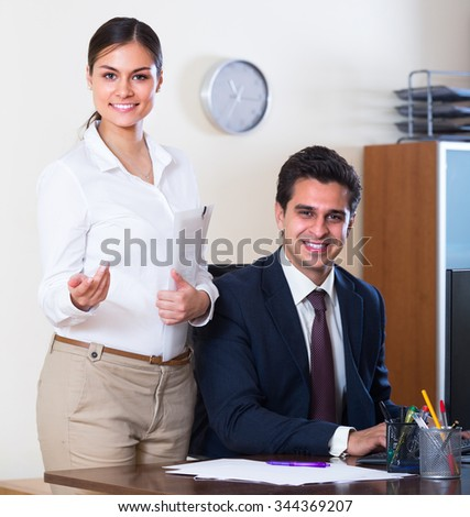 Smiling businessman and secretary working in modern office