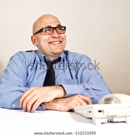 Smiling businessman at office desk with telephone. Wheeler dealer or business crook.