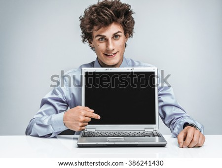 Smiling businessman at the workplace looking at camera and showing at screen laptop. Business concept  - stock photo