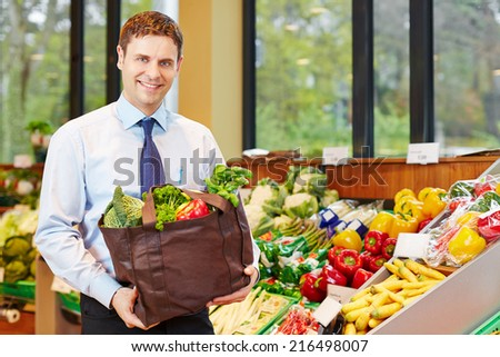 Smiling businessman buying bag of fresh vegetables in organic food store