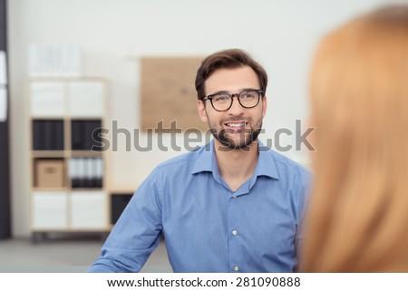 Smiling businessman chatting to a female team member as they work together in the office, view of his face past her hair - stock photo