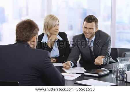 Smiling businessman discussing document at meeting with coworkers.