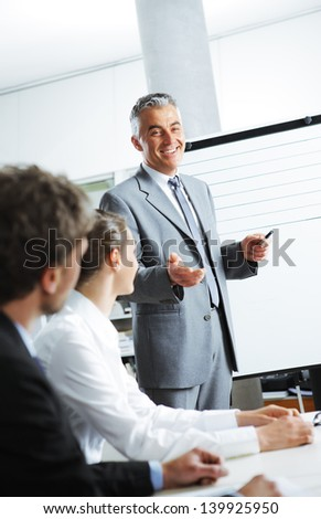 Smiling businessman discussing plans with his colleagues in board meeting - stock photo