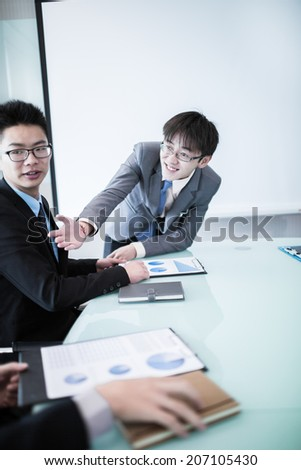 Smiling businessman discussing plans with his colleagues in board meeting.asian