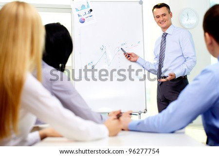 Smiling businessman drawing a graph for his colleagues on the whiteboard - stock photo