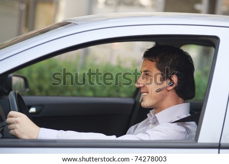 Smiling businessman driving a car with blue-tooth hands-free