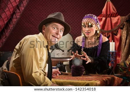 Smiling businessman getting his fortune from pretty gypsy woman