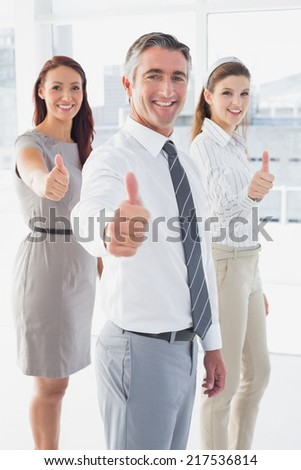 Smiling businessman giving thumbs up with co-workers