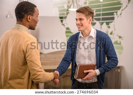 Smiling businessman handshaking with his colleague. Back view. - stock photo