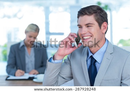 Smiling businessman having a phone call in his office - stock photo