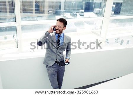 Smiling businessman having mobile phone conversation while standing with digital tablet in office building, happy intelligent man in suit talking on cell telephone and holding touch pad in the hand - stock photo