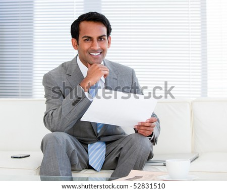 Smiling businessman holding a note in the office - stock photo