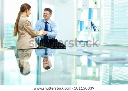 Smiling businessman holding affectionately his female colleague'??s hand as a sign of trust and support