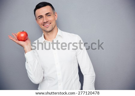 Smiling businessman holding apple on palm over gray background and looking at camera - stock photo