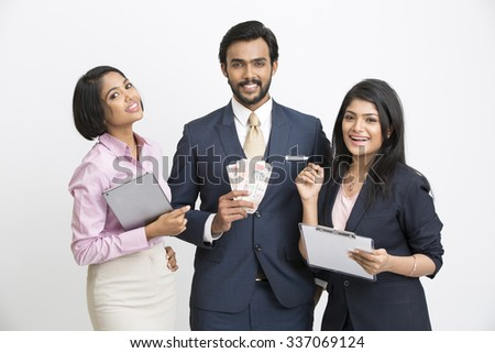Smiling businessman holding money standing with his colleagues on white background.